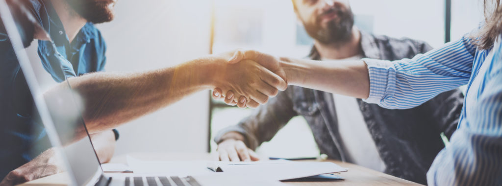 Business partnership handshake concept.Photo two coworkers handshaking process. Successful deal after great meeting. Horizontal, blurred background.Wide